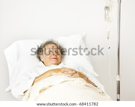 Senior woman sleeping in a hospital bed.