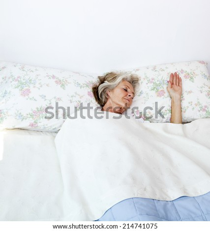 Senior woman sleeping in bed at home - stock photo