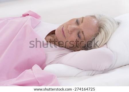 senior woman sleeping on bed - stock photo