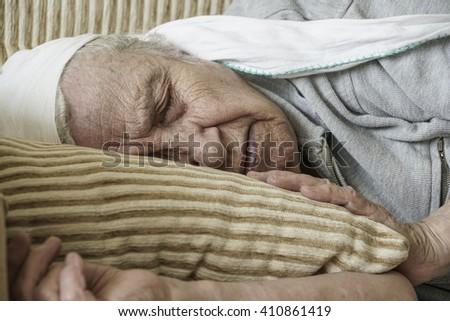senior woman sleeping on sofa - stock photo