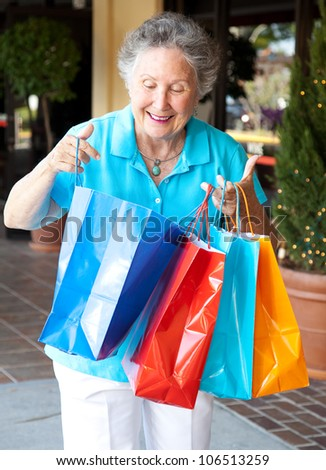 Senior woman smiles as she looks into her shopping bags to check out what she's bought. - stock photo
