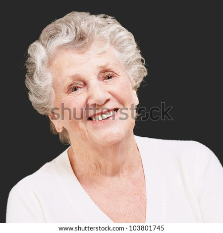 senior woman smiling against a black background - stock photo