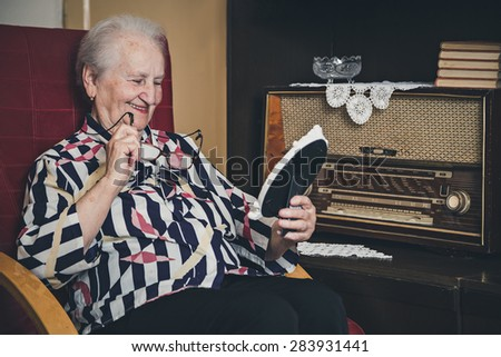 Senior woman smiling and looking at old photo frame - stock photo