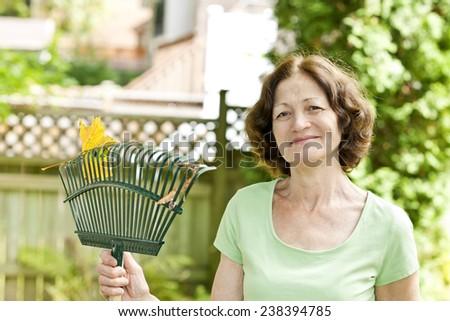 Senior woman smiling holding rake for yard work outside - stock photo