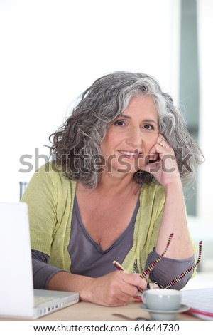 Senior woman smiling in front of a computer