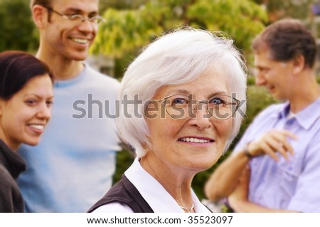 Senior woman smiling in front of three young people, outdoor - stock photo