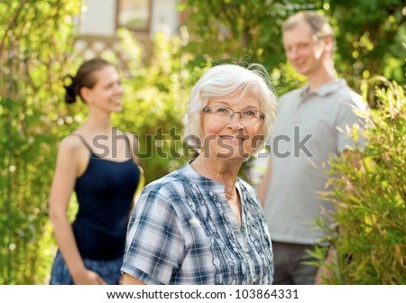 Senior woman smiling in front of two young people, outdoors - stock photo