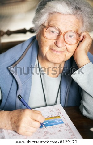 Senior woman solving crossword puzzle, portrait - stock photo