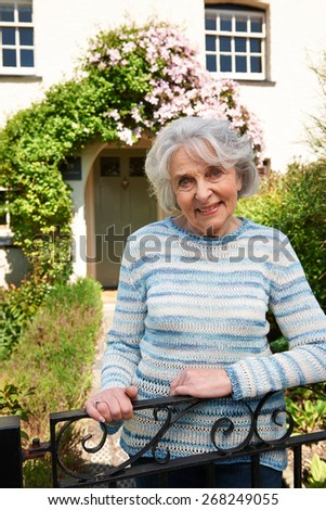 Senior Woman Standing Outside Pretty Cottage