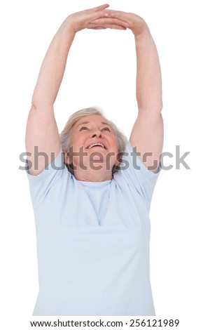 Senior woman stretching her arms on white background - stock photo