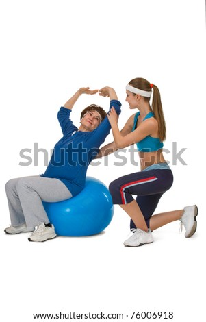 senior woman stretching on fitball with trainer - stock photo