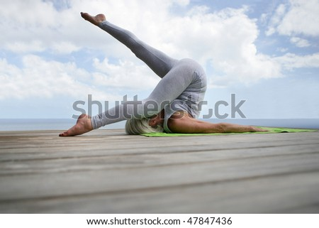 Senior woman stretching outside on a pontoon