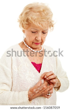 Senior woman struggles to button her sweater because of painful arthritis.  Isolated on white.   - stock photo