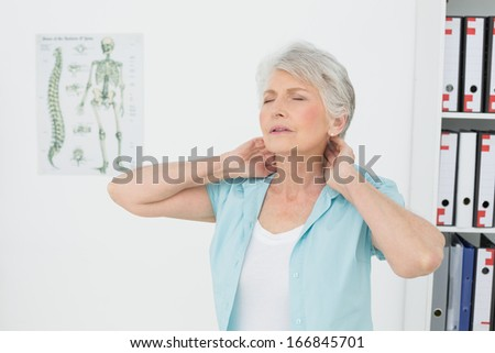 Senior woman suffering from neck pain with eyes closed in the medical office - stock photo