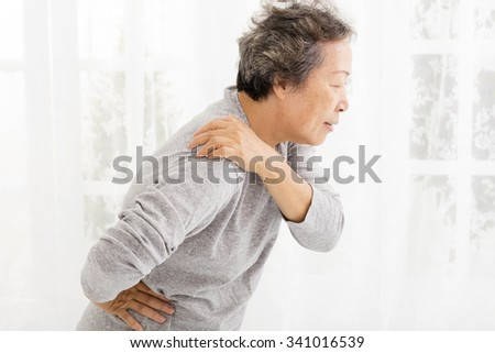 senior woman suffering in shoulder pain - stock photo