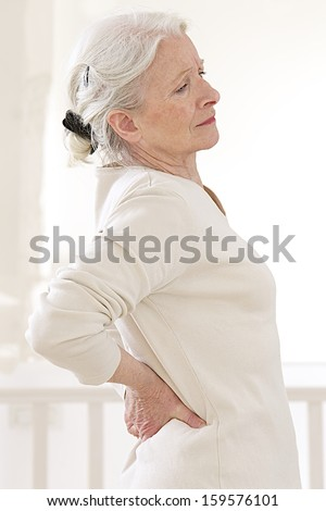 senior woman suffers from backache. - Mature female has pain in back  - stock photo
