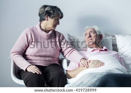 Senior woman supporting her ill husband lying in a hospital bed - stock photo