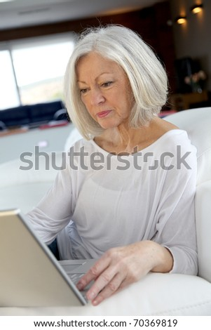 Senior woman surfing on internet at home - stock photo