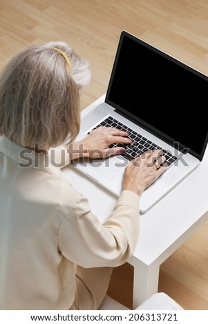Senior woman surfing the net on laptop at home - stock photo