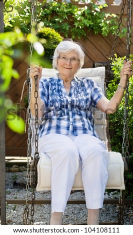 Senior woman  swinging on a garden-swing in summer - stock photo