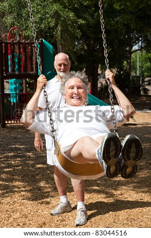 Senior woman swinging on the playground in the park.  Her husband is pushing her. - stock photo