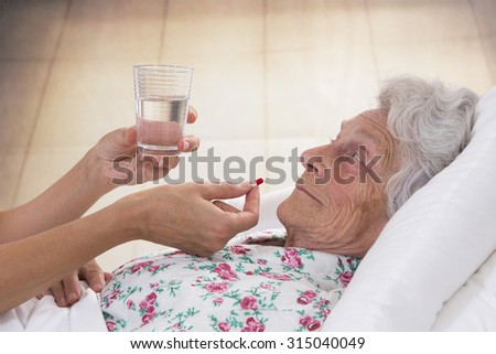 senior woman taking medical pill with a cup of water