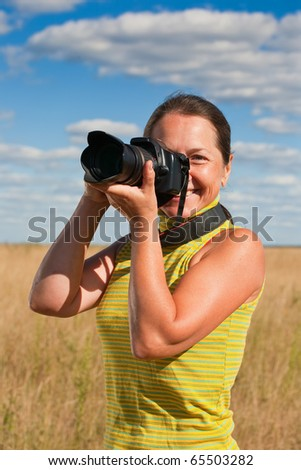 Senior woman taking photo with camera against field