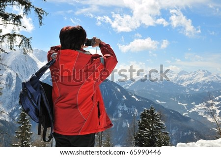 Senior woman taking picture with camera in mountain winter snow landscape - stock photo