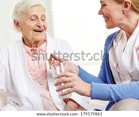 Senior woman taking pill with water from geriatric nurse - stock photo