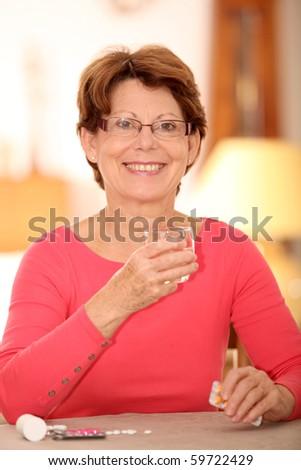Senior woman taking pills - stock photo