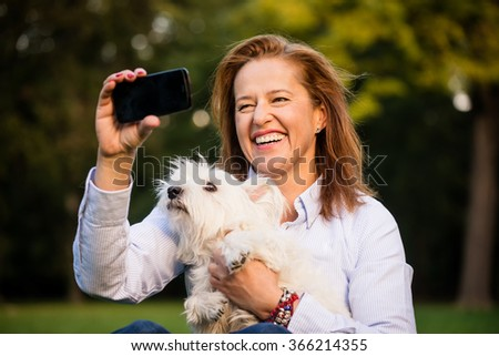 Senior woman taking selfie of herself and her dog by mobile phone in nature - stock photo