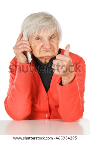 Senior woman talking on mobile phone and holding her thumbs up