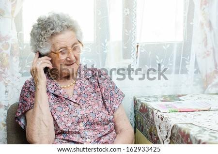 senior woman talking on phone indoor - stock photo