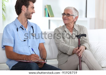 Senior woman talking to a young medic - stock photo