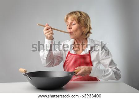 Senior woman tasting some food - stock photo