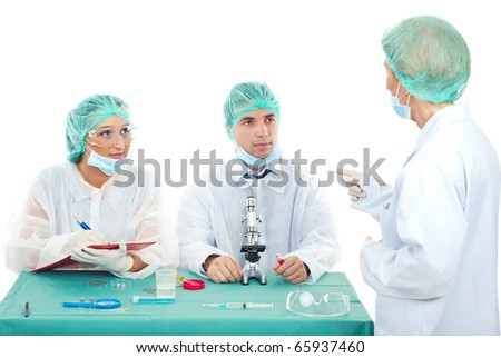 Senior woman teacher explaining to two students in laboratory and pointing - stock photo