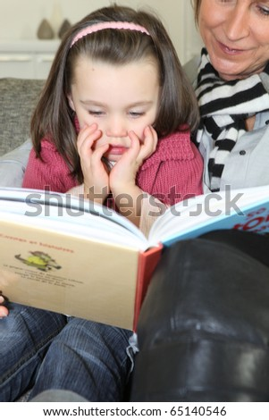 Senior woman telling a story to a little girl - stock photo
