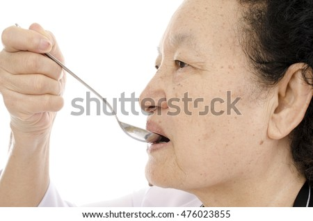 Senior woman testing food over white background