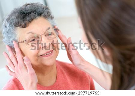 Senior woman testing glasses - stock photo
