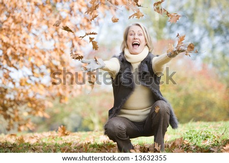 Senior woman throwing autumn leaves in the air - stock photo
