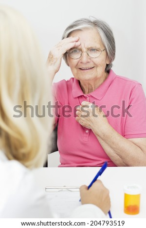 Senior woman touching her head talking with  doctor. - stock photo