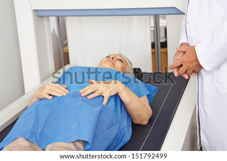 Senior woman under DPX machine for bone density measurement in a hospital - stock photo
