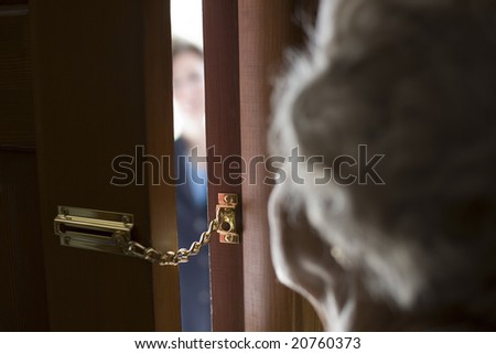 Senior woman using a security chain on front door - stock photo