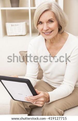 Senior woman using a tablet computer at home  - stock photo