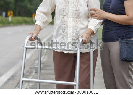 senior woman using a walker cross street - stock photo