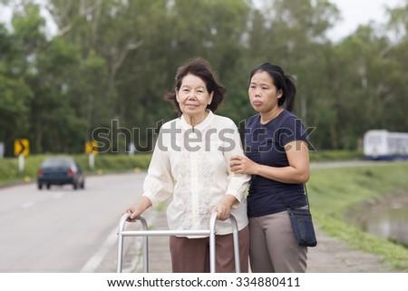 senior woman using a walker cross street - stock photo