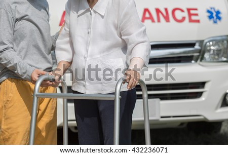 senior woman using a walker with caregiver to take ambulance