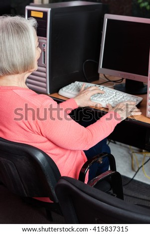 Senior Woman Using Computer At Desk In Classroom - stock photo