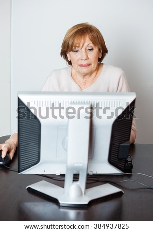 Senior Woman Using Computer In Class - stock photo