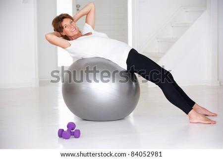 Senior woman using gym ball - stock photo